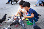 Hochiminh City, Vietnam - July 14, 2015: two babies for feeding pigeons on the streets of Saigon — Stock Photo