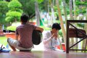 Hochiminh City, Vietnam - June 21, 2015: undefined, two boys playing guitar and flute l in a park in Ho Chi Minh City, Vietnam — Stock Photo