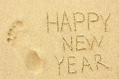 Inscription 'HAPPY NEW YEAR' and human footprint in the sand on the beach — Stock Photo