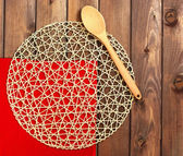Round rope napkin or stand, red place mat  and spoon on a wooden — Stock Photo
