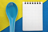 Menu background. Cook book. Recipe notebook on a blue and yellow background. Clay spoon and Notepad. — Stock Photo