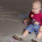 Little boy draws with chalk on the pavement sun — Stock Photo #78552452