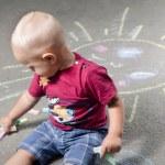 Little boy draws with chalk on the pavement sun — Stock Photo #78552482