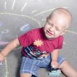 Little boy draws with chalk on the pavement sun — Stock Photo #78552512