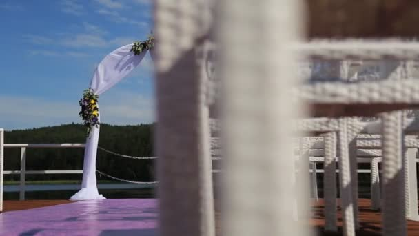 larche de mariage avec des fleurs est vu travers les chaises de canne en bois situ sur le cot du lac avec beau paysage squence - Cout Fleuriste Mariage