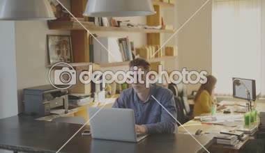 Young hipster working at his studio loft. — Stock Video