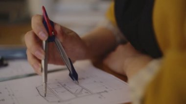 Close-up Young female architect working on blueprint using the compass and enter the data into an electronic tablet — Stock Video
