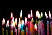 Rainbow color candle on black background — Stock Photo