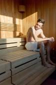 Muscular man sitting in a sauna — Stock Photo