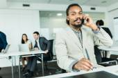Handsome graphics designer talking on the phone — Stock Photo