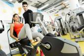 Woman instructed by a man in a gym — Stock Photo