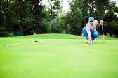Golf-spelare märkning bollen på putting greenen — Stockfoto