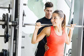 Trainer giving instructions to a woman in a gym — Stock Photo