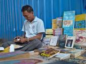 YANGON, MYANMAR - DECEMBER 23, 2013: A street bookseller sits among his books as he makes a repair — Stock Photo