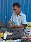 YANGON, MYANMAR - DECEMBER 23, 2013: Street bookseller repairs a paperback book near his business location — Stock Photo