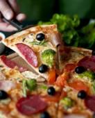 Pizza Slice with salami, broccoli, tomato, olives — Stock Photo