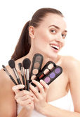 Beautiful smiling woman with set of brushes and palette of color — Stock Photo