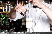 Young handsome barista making latte behind the bar in cafe. — Stock Photo