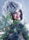 Winter schoonheid vrouw in een bont hoed gluurt — Stockfoto
