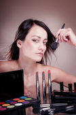 Beautiful girl with  brush near the face — Stock Photo