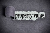 Property value word under torn black sugar paper — Stock Photo