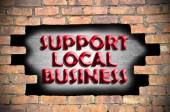 Support local business in the hole of brick wall — Stock Photo