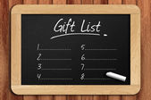 Chalkboard on the wooden table written gift list — Stock Photo