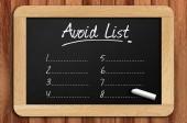 Chalkboard on the wooden table written avoid list — Stock Photo