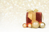 Christmas gift and baubles with golden lights — Stock Photo
