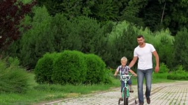 Father teaching his son to ride a bike — Stock Video