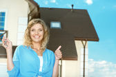 Happy girl with keys next to her new house — Stock Photo