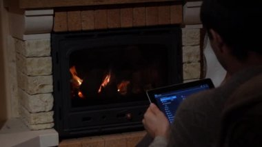 Man Is Using His Tablet In Front Of A Fireplace Technology and Home Concept — Stock Video