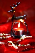 Christmas decoration with burning tea light and beads on red — Stock Photo