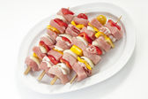 Raw shashlik skewers on plate, elevated view — Stock Photo