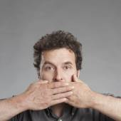 Mature man covering mouth — Stock Photo