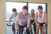 Senior women using spinning bikes — Stock Photo
