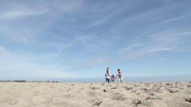 Mamma och pappa kör längs stranden med sina barn — Stockvideo