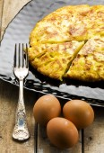 Sliced omelet on black plate and whole brown eggs on rustic wooden table — Stock Photo