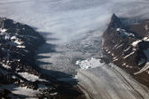 Aerial view of a glacier flowing from the mountains into the Arctic ocean in Greenland — Stock Photo