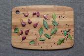 Garlic cloves, bay leaves and black pepper on the board — Stock Photo
