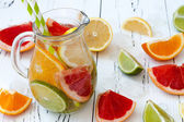 Detox citrus infused flavored water. Refreshing summer homemade cocktail with lemon, lime, orange and grapefruit — Stock Photo