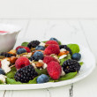 Summer refreshing spinach mixed berry salad with pumpkin and sunflower seeds, almonds, feta cheese and sweet red raspberry vinaigrette. Copy space background — Foto Stock #81269046