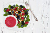 Summer refreshing spinach mixed berry salad with pumpkin and sunflower seeds, almonds, feta cheese and sweet red raspberry vinaigrette. Copy space background — Stock Photo