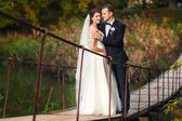 Bride and groom on the bridge over river — Stock Photo