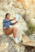 Hiking beautiful young girl resting in the mountains in the hands holding the tablet. — Stock Photo