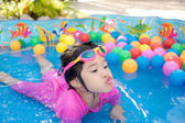 Baby girl playing in kiddie pool — Stock Photo