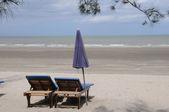 Deck chair and umbrella on beach — Stock Photo