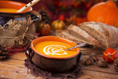 Homemade pumpkin soup on a rustic table with autumn decorations — Stock Photo