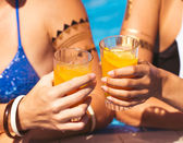 Girlfriends clinking glasses with cocktails at the poolside — Stock Photo
