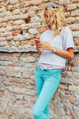 Blonde with beautiful styling with pink smartphone and aqua jean — Stock Photo